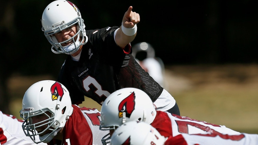 New Arizona Cardinals'  quarterback Carson Palmer shouts instructions at the line of scrimmage during a voluntary Cardinals football mini camp, on Tuesday, April 23, 2013, in Tempe, Ariz. (AP Photo/Ross D. Franklin)