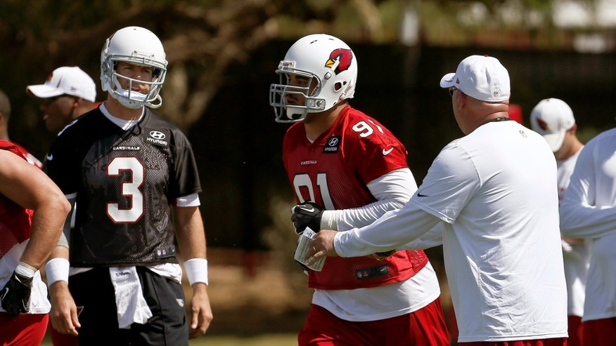 Arizona Cardinals new quarterbacks Carson Palmer (3) listens to head coach Bruce Arians, right, as Matt Shaughnessy (91) runs past during the team's NFL football minicamp, on Tuesday, April 23, 2013, in Tempe, Ariz. (AP Photo/Ross D. Franklin)