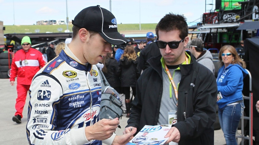 NASCAR Sprint Cup Series driver Brad Keselowski, left, signs autographs in the garage area at Kansas Speedway in Kansas City, Kan., Friday, April 19, 2013. (AP Photo/Colin E. Braley)