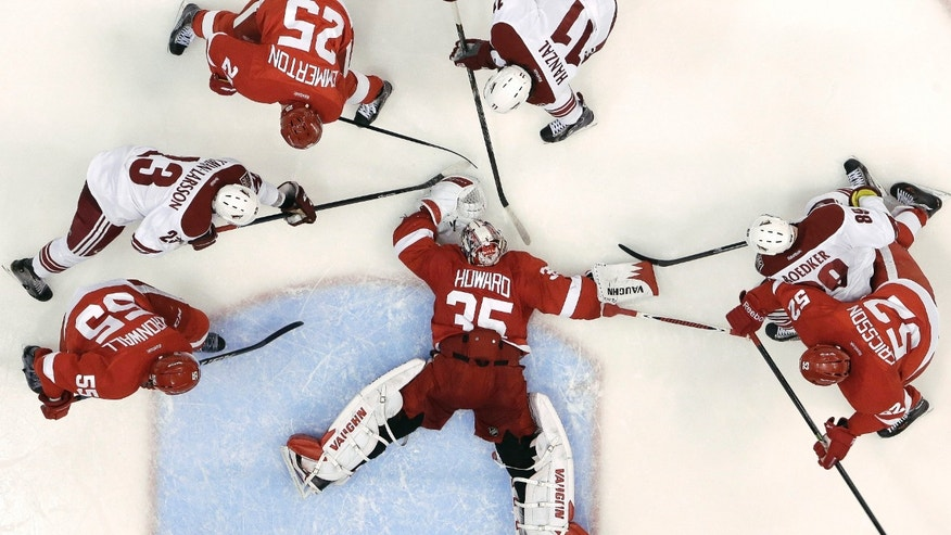 Detroit Red Wings goalie Jimmy Howard (35) covers the puck against the Phoenix Coyotes in the second period of an NHL hockey game in Detroit, Monday, April 22, 2013. Detroit won 4-0. (AP Photo/Paul Sancya)