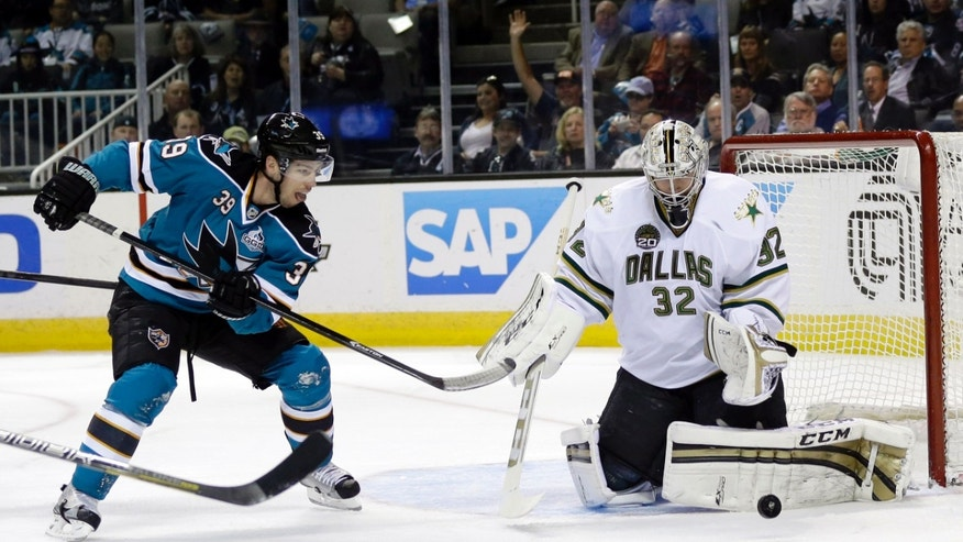 Dallas Stars goalie Kari Lehtonen, of Finland, right, stops a shot next to San Jose Sharks center Logan Couture (39) during the first period of an NHL hockey game in San Jose, Calif., Tuesday, April 23, 2013. (AP Photo/Marcio Jose Sanchez)