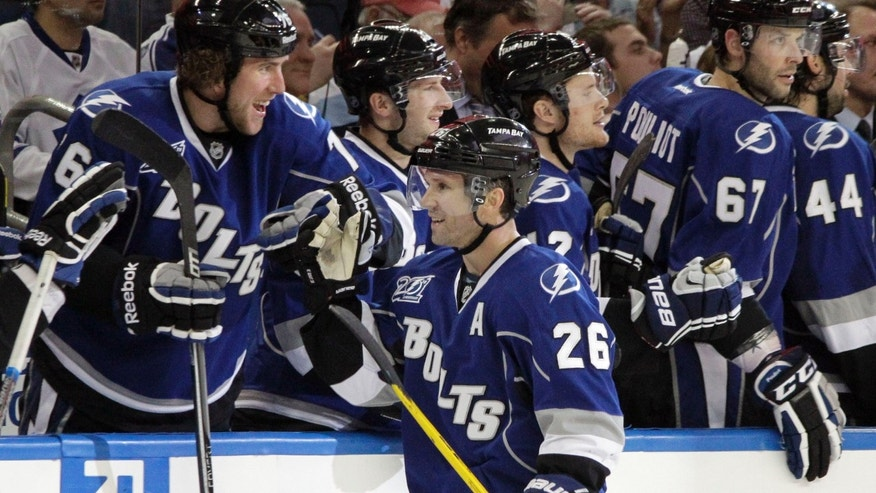 Tampa Bay Lightning right wing Martin St. Louis (26) gets high fives from the bench after his goal against the Toronto Maple Leafs during the third period of an NHL hockey game Wednesday, April 24, 2013, in Tampa, Fla. (AP Photo/Chris O'Meara)