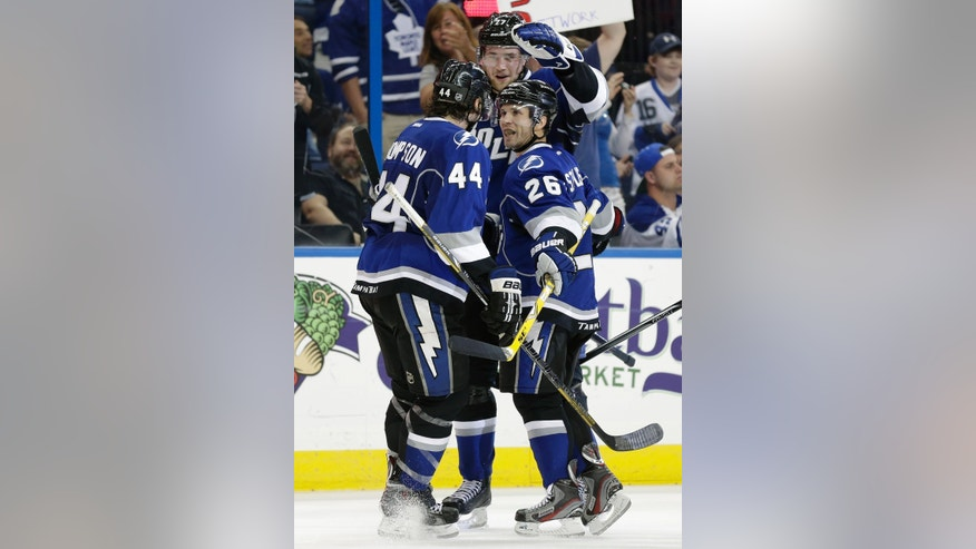Tampa Bay Lightning right wing Martin St. Louis (26) celebrates with teammates center Nate Thompson and defenseman Victor Hedman, of Sweden, after scoring against the Toronto Maple Leafs during the second period of an NHL hockey game Wednesday, April 24, 2013, in Tampa, Fla. (AP Photo/Chris O'Meara)