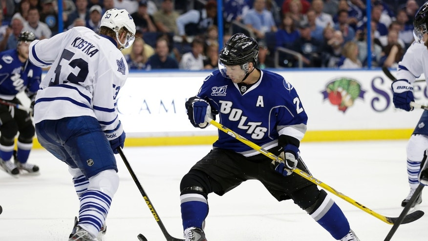 Tampa Bay Lightning right wing Martin St. Louis (26) kicks the puck away from Toronto Maple Leafs defenseman Mike Kostka (53) during the third period of an NHL hockey game Wednesday, April 24, 2013, in Tampa, Fla. The Lightning won the game 5-2. (AP Photo/Chris O'Meara)