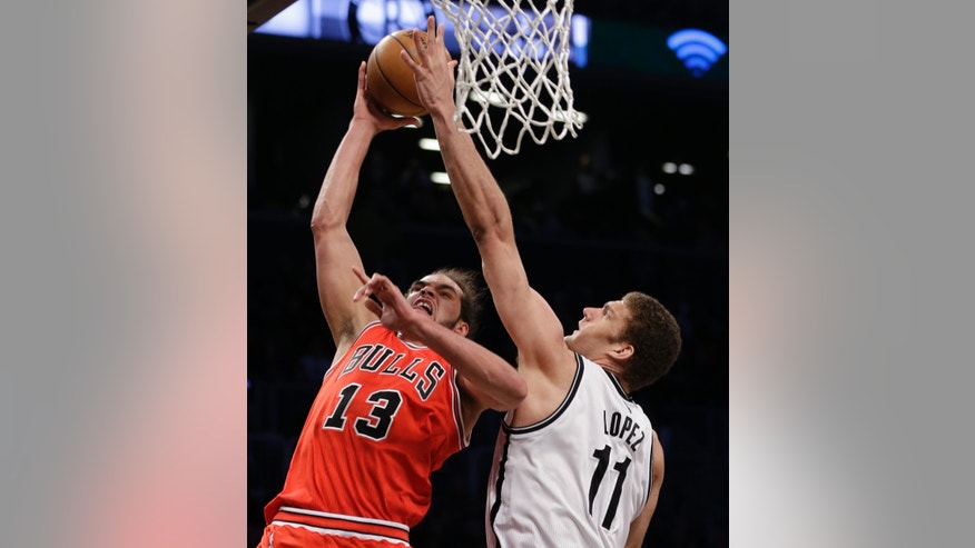 Brooklyn Nets center Brook Lopez (11) defends a shot by Chicago Bulls center Joakim Noah (13) in the second half of Game 2 of their first-round NBA basketball playoff series, Monday, April 22, 2013, in New York. The Bulls won 90-82. (AP Photo/Kathy Willens)