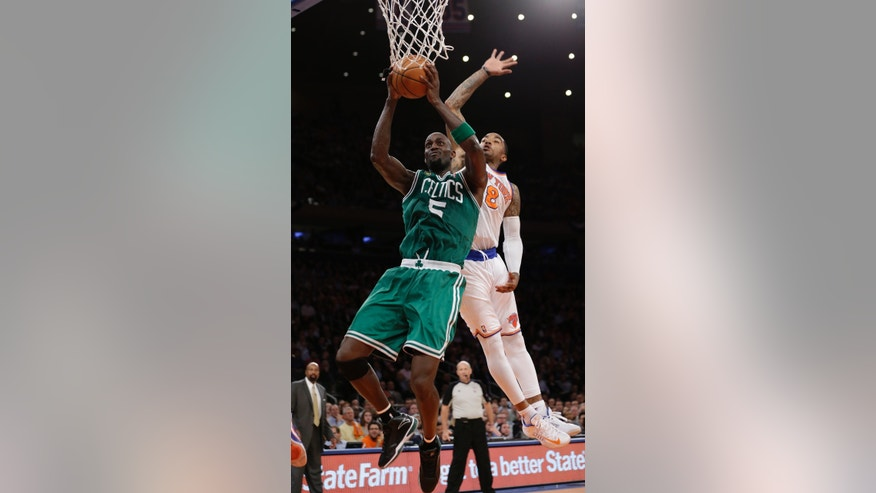 Boston Celtics center Kevin Garnett (5) goes to the basket past New York Knicks guard J.R. Smith (8) in the second half of Game 2 of their first-round NBA basketball playoff series in New York, Tuesday, April 23, 2013. The Knicks won 87-71. (AP Photo/Kathy Willens)