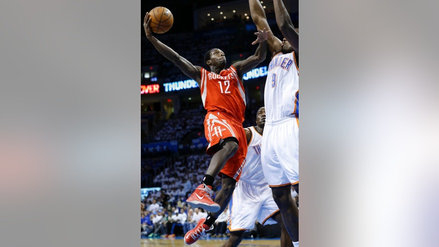 Houston Rockets guard Patrick Beverly shoots against Oklahoma City Thunder center Kendrick Perkins (5) and forward Serge Ibaka (9) in the first quarter of Game 2 in their first-round NBA basketball playoff series in Oklahoma City, Wednesday, April 24, 2013. (AP Photo/Sue Ogrocki)