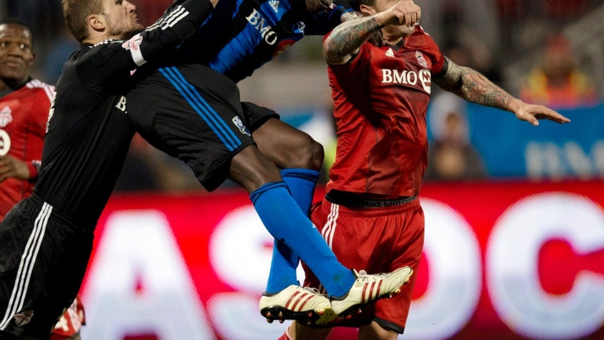 Toronto FC goalie Stefan Frei, left, leaps in as Danny Califf, right, battles for the ball with Montreal Impact's Hassoum Camara during the second half of their Amway Canadian Championship qualifying soccer match, Wednesday, April 24, 2013, in Toronto. The tournament winner will represent Canada in the CONCACAF Champions League. (AP Photo/The Canadian Press, Frank Gunn)