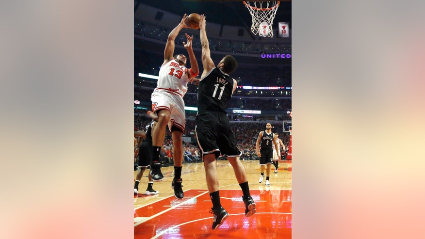 Chicago Bulls center Joakim Noah (13) shoots over Brooklyn Nets center Brook Lopez during the first half of Game 3 of their first-round NBA basketball playoff series, Thursday, April 25, 2013, in Chicago. (AP Photo/Charles Rex Arbogast)
