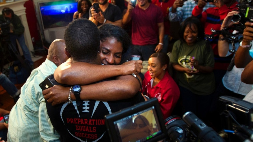 D.J. Hayden from Houston, left, hugs his mother Tori Hayden after he was selected 12th overall by the Oakland Raiders in the NFL football draft at his house in Missouri City, Texas. (AP Photo/Houston Chronicle, Cody Duty)