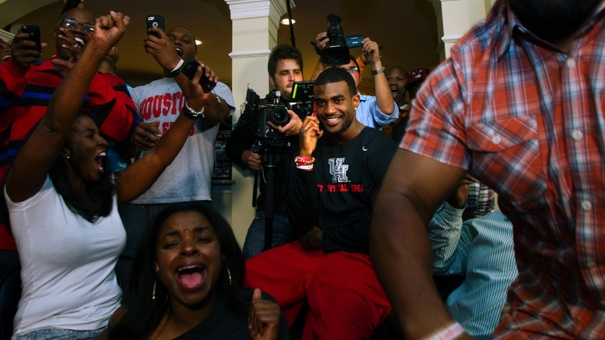 D.J. Hayden from Houston, center, smiles as he receives a call from the Oakland Raiders telling him he was selected 12th overall in the NFL football draft at his house in Missouri City, Texas. (AP Photo/Houston Chronicle, Cody Duty)