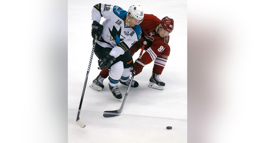 San Jose Sharks' Patrick Marleau (12) battles Phoenix Coyotes' Mikkel Bodker (89) for the puck during the second period of an NHL hockey game on Wednesday, April 24, 2013, in Glendale, Ariz. (AP Photo/Matt York)
