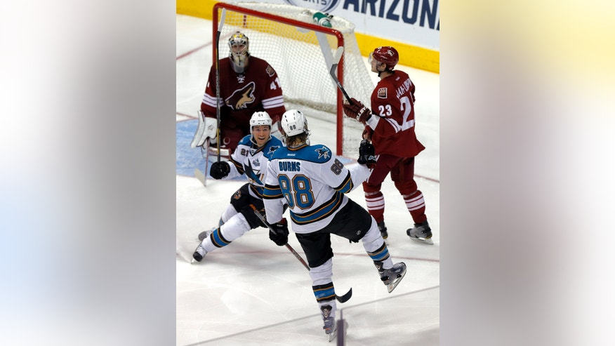 San Jose Sharks' Brent Burns (88) celebrates his goal with teammate T.J. Galiardi (21) as Phoenix Coyotes' Oliver Ekman-Larsson (23) and goalie Mike Smith look on during the second period of an NHL hockey game on Wednesday, April 24, 2013, in Glendale, Ariz. (AP Photo/Matt York)