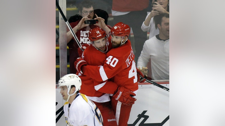 Detroit Red Wings center Pavel Datsyuk (13), left, is congratulated by teammate Henrik Zetterberg (40), of Sweden, behind Nashville Predators right wing Daniel Bang after making a goal during the second period of an NHL hockey game against the Nashville Predators in Detroit, Thursday, April 25, 2013. (AP Photo/Carlos Osorio)
