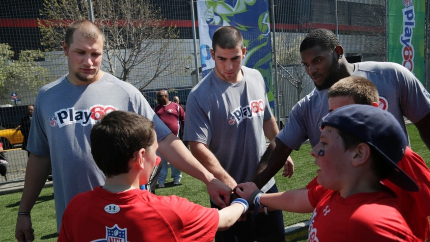 NFL draft prospects Eric Fisher of Central Michigan, center, Lane Johnson of Oklahoma, left, and Sharrif Floyd of Florida participate in a youth football clinic in New York, Wednesday, April 24, 2013.The draft begins Thursday in New York. (AP Photo/Seth Wenig)