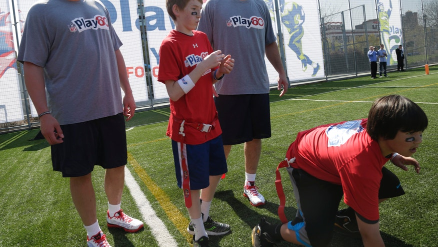 NFL draft prospects Eric Fisher of Central Michigan, second from right, and Lane Johnson of Oklahoma, left, participate in a youth football clinic in New York, Wednesday, April 24, 2013. The draft begins Thursday in New York. (AP Photo/Seth Wenig)