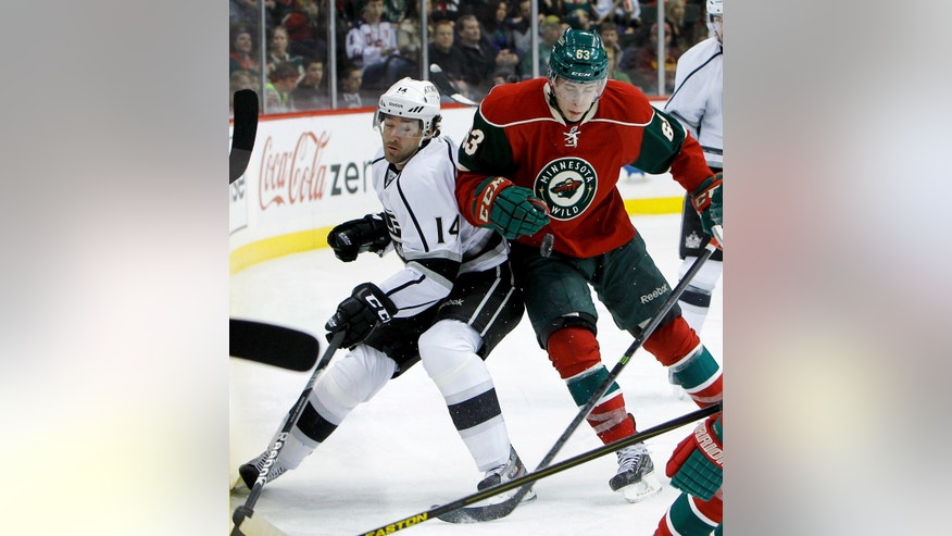 Los Angeles Kings right wing Justin Williams, left, and Minnesota Wild right wing Charlie Coyle, right, collide as they battle for the puck during the second period of an NHL hockey game in St. Paul, Minn., Tuesday, April 23, 2013. (AP Photo/Ann Heisenfelt)