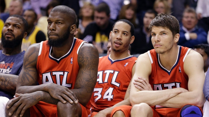 From left, Atlanta Hawks forward Ivan Johnson, guard Devin Harris and forward Kyle Korver watch front the bench late in the second half of Game 2 of a first-round NBA basketball playoff series against the Indiana Pacers in Indianapolis, Wednesday, April 24, 2013. The Pacers won 113-98. (AP Photo/Michael Conroy)