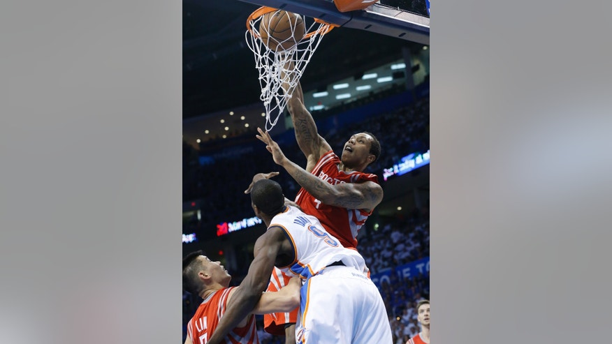 Houston Rockets center Greg Smith (4) dunks in front of teammate Jeremy Lin (7) and Oklahoma City Thunder forward Serge Ibaka (9) in the second quarter of Game 2 of their first-round NBA basketball playoff series in Oklahoma City, Wednesday, April 24, 2013. (AP Photo/Sue Ogrocki)