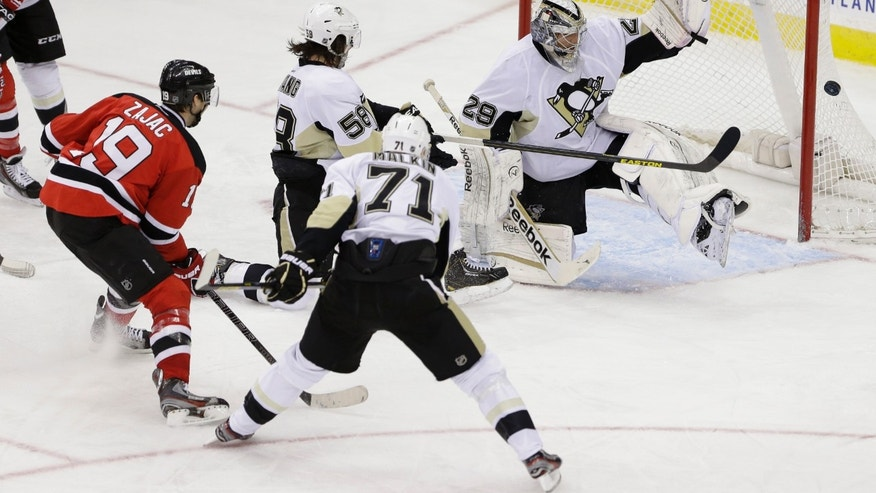 Pittsburgh Penguins goalie Marc-Andre Fleury, right, deflects a shot by New Jersey Devils center Travis Zajac, left, as Kris Letang (58) and Evgeni Malkin (71), of Russia, defend during the third period of an NHL hockey game, Thursday, April 25, 2013, in Newark, N.J. The Devils won 3-2. (AP Photo/Julio Cortez)