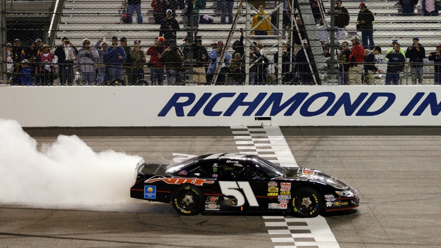 Kyle Busch performs a burnout as he celebrates winning the Denny Hamlin's Charity Race at Richmond International Raceway in Richmond, Va., Thursday April 25, 2013. (AP Photo/Steve Helber)