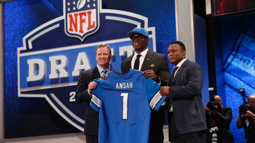 Ezekiel Ansah, from Brigham Young, stands with NFL Commissioner Roger Goodell, left, and Barry Sanders after being selected fifth overall by the Detroit Lions in the first round of the NFL football draft, Thursday, April 25, 2013, at Radio City Music Hall in New York. (AP Photo/Jason DeCrow)