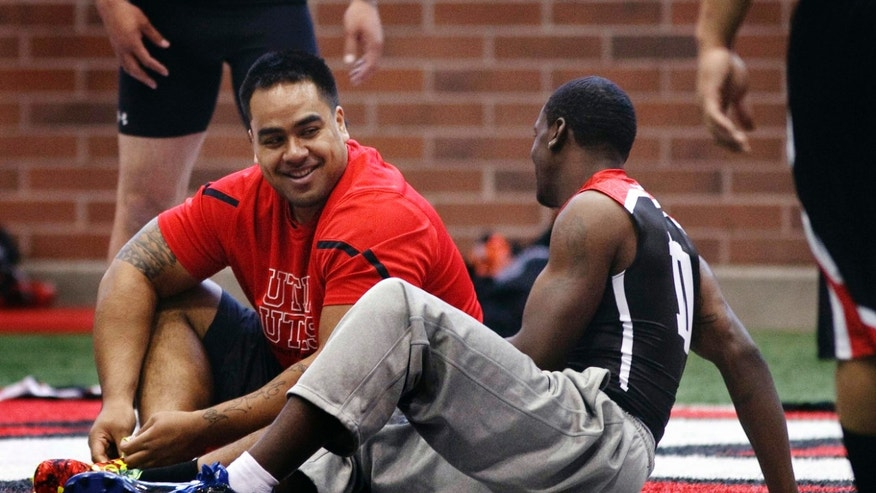 FILE - This March 20, 2013, file photo, Defensive lineman Star Lotulelei and wide receiver DeVonte Christopher talk between performances during Utah's NFL football pro day, in Salt Lake City. Lotulelei won't be among the two dozen players attending the NFL draft in person in New York. He declined the invitation so he could be with 50 to 100 family members and friends at his home south of Salt Lake City. (AP Photo/The Salt Lake Tribune, Leah Hogsten, File)  DESERET NEWS OUT; LOCAL TV OUT; MAGS OUT