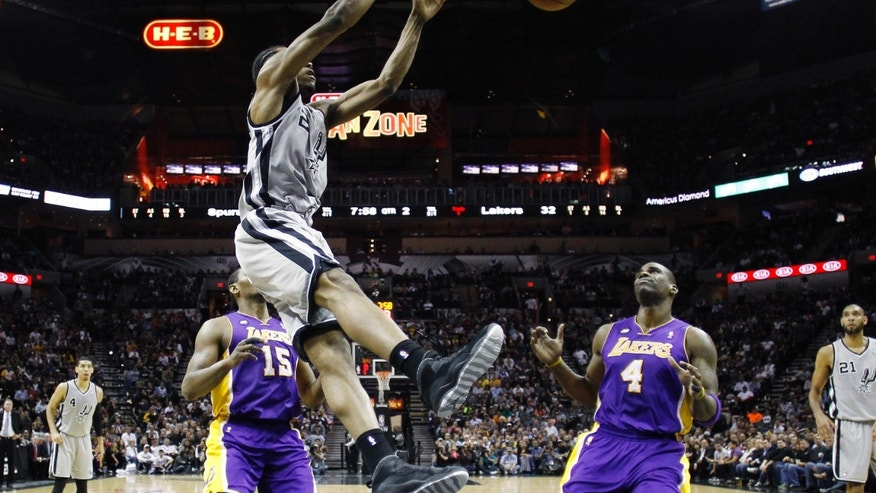San Antonio Spurs' Kawhi Leonard (2) scores over Los Angeles Lakers' Antawn Jamison (4) and Metta World Peace (15) during the first half of Game 2 of a first-round NBA basketball playoff series on Wednesday, April 24, 2013, in San Antonio, Texas. (AP Photo/Eric Gay)