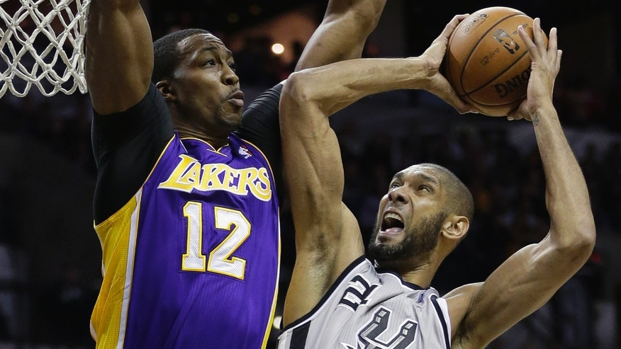 San Antonio Spurs' Tim Duncan (21) is defended by Los Angeles Lakers' Dwight Howard (12) while trying to score during the first half of Game 2 of a first-round NBA basketball playoff series on Wednesday, April 24, 2013, in San Antonio, Texas. (AP Photo/Eric Gay)