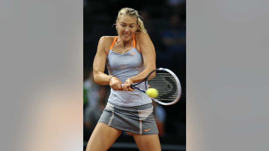 Maria Sharapova from Russia hits a backhand against Lucie Safarova from Czech Republic in her second round match of the WTA tennis tournament in Stuttgart, Germany, Thursday, April 25, 2013. (AP Photo/Daniel Maurer)