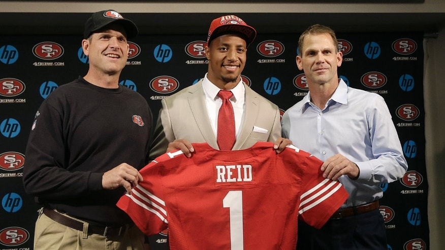 Safety Eric Reid, the first-round draft pick of the San Francisco 49ers, center, holds up a jersey with head coach Jim Harbaugh, left, and general manager Trent Baalke during a news conference at the team's training facility in Santa Clara, Calif., Friday, April 26, 2013. (AP Photo/Jeff Chiu)