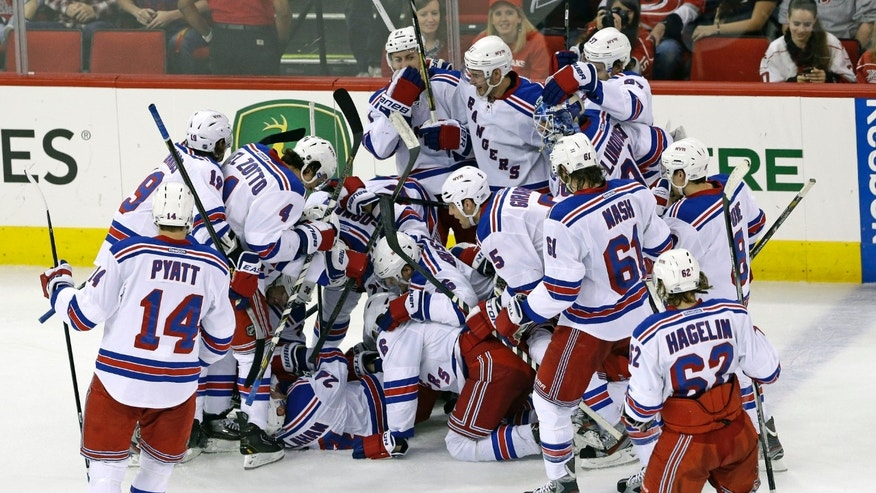 The New York Rangers celebrate Ryan Callahan's overtime goal to defeat the Carolina Hurricanes in an NHL hockey game in Raleigh, N.C., Thursday, April 25, 2013. New York won 4-3. (AP Photo/Gerry Broome)