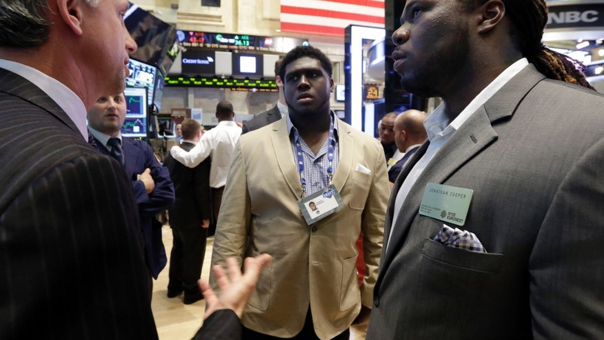 NFL draft prospects Chance Warmack, center, of Alabama, and Jonathan Cooper, of North Carolina, talk with specialist Donald Himpele during their visit to the trading floor of the New York Stock Exchange, Wednesday, April 24, 2013.  (AP Photo/Richard Drew)
