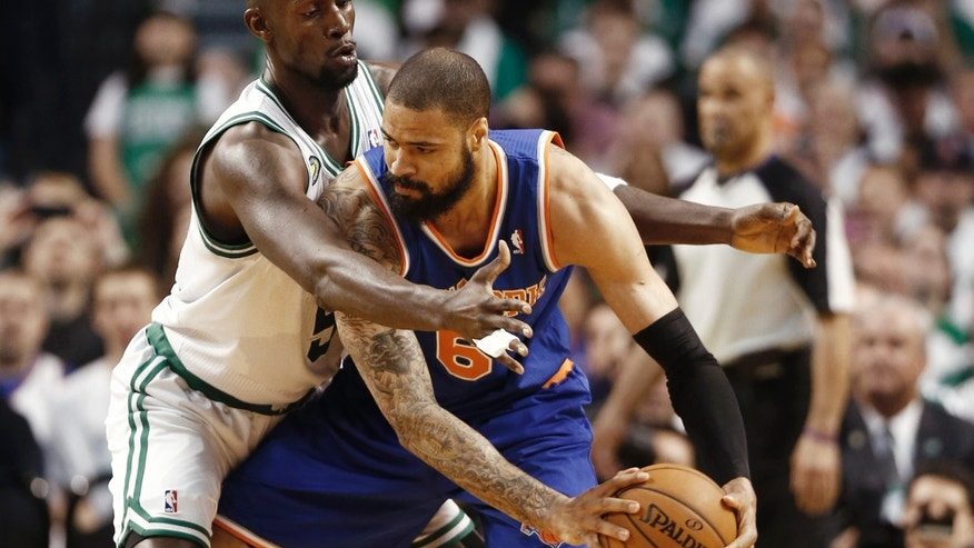 New York Knicks center Tyson Chandler looks for an opening around Boston Celtics' Kevin Garnett during the first quarter of Game 3 of a first round NBA basketball playoff series in Boston Friday, April 26, 2013. (AP Photo/Winslow Townson)