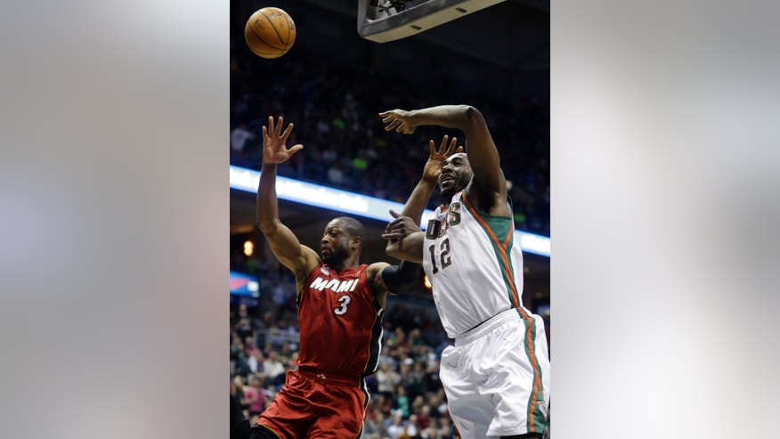 Miami Heat's Dwyane Wade, left, knocks the ball away from Milwaukee Bucks' Luc Richard Mbah a Moute (12) during the second half of Game 3 in their first-round NBA basketball playoff series on Thursday, April 25, 2013, in Milwaukee. (AP Photo/Morry Gash)