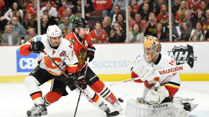 Calgary Flames goalie Joey MacDonald, right, swats the puck away as Chicago Blackhawks' Patrick Sharp, center, tries to score and Flames' Mark Giordano defends during the second period of an NHL hockey game, Friday, April 26, 2013 in Chicago.  (AP Photo/Brian Kersey)