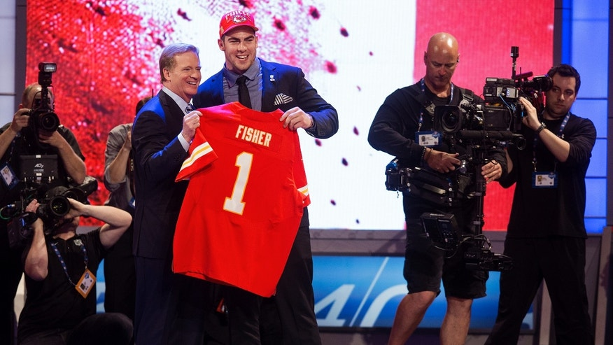 April 25, 2013: Eric Fisher, right, from Central Michigan, stands with NFL Commissioner Roger Goodell after being selected first overall by the Kansas City Chiefs during the first round of the NFL football draft at Radio City Music Hall in New York.