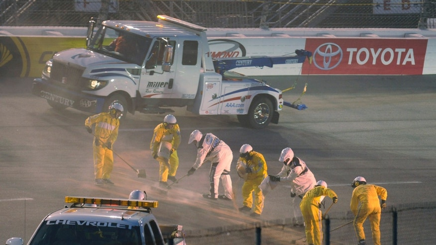 A cleanup crew works to clean the track after a spinout during the Nationwide race at Richmond International Raceway in Richmond, Va., Friday April 26, 2013.   (AP Photo/Clem Britt)
