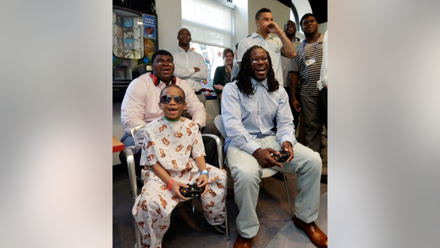 Pediatric patient Tyreke Whigham, 8, plays a video game with top NFL draft prospects DJ Fluker, from Alabama, seated left, and Eddie Lacy, of Alabama, seated right, during their visit to the Kravis Children's Hospital of New York's Mount Sinai Medical Center,  Thursday, April 25, 2013. (AP Photo/Richard Drew)
