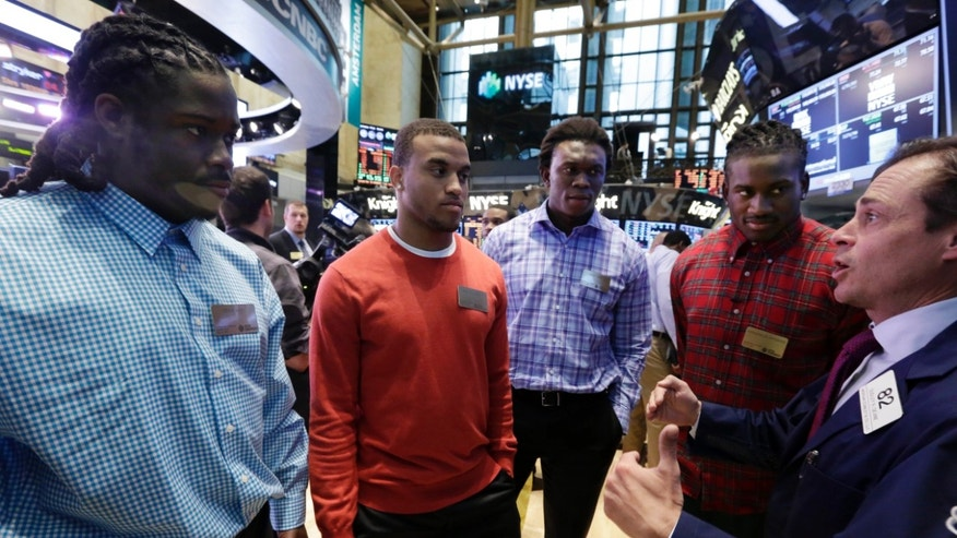 NFL draft prospects , from left, Eddie Lacy, Alabama; Dee Milliner, Alabama; Ezekiel Ansah, Brigham Young; and Cordarrelle Patterson, Tennessee, visit the trading floor of the New York Stock Exchange, and talk with trader Dudley Devine, Wednesday, April 24, 2013.  (AP Photo/Richard Drew)