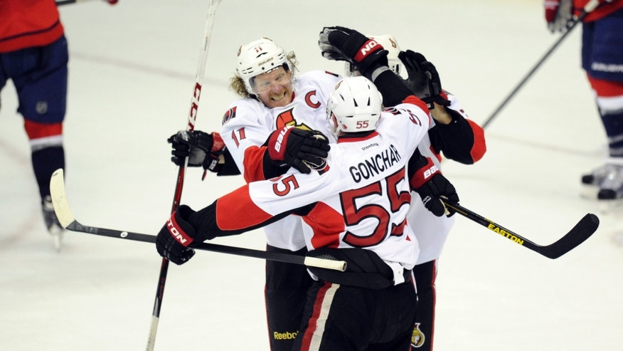 Ottawa Senators defenseman Sergei Gonchar (55) celebrates his game-winning goal in the overtime period of an NHL hockey game with teammate Daniel Alfredsson (11) against the Washington Capitals, Thursday, April 25, 2013, in Washington. (AP Photo/Nick Wass)