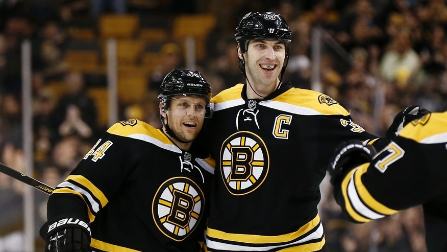 Boston Bruins' Dennis Seidenberg, left, celebrates his goal with Zdeno Chara during the second period of an NHL hockey game against the Tampa Bay Lightning in Boston, Thursday, April 25, 2013. (AP Photo/Winslow Townson)