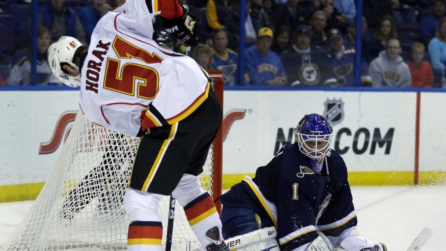 Calgary Flames' Roman Horak, of the Czech Republic, skates past the puck as it is stopped by St. Louis Blues goalie Brian Elliott, right, during the third period of an NHL hockey game, Thursday, April 25, 2013, in St. Louis. The Blues won 4-1. (AP Photo/Jeff Roberson)