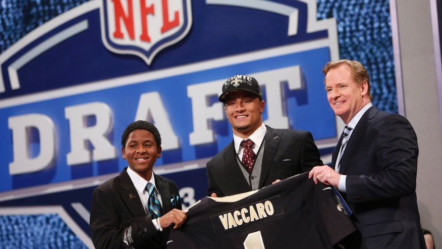 Kenny Vaccaro, from Texas, stands with NFL Commissioner Roger Goodell, right, and Markell Gregoire, 13, a patient at St. Jude Children's Research Hospital, after being selected 15th overall by the New Orleans Saints in the first round of the NFL football draft, Thursday, April 25, 2013, at Radio City Music Hall in New York. (AP Photo/Jason DeCrow)
