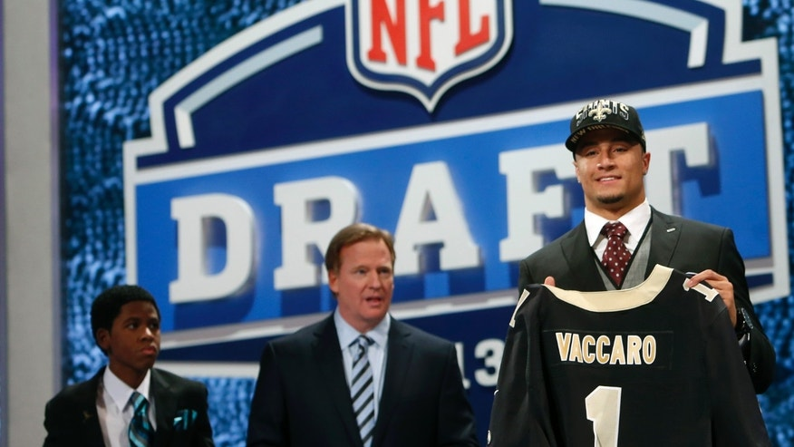 Safety Kenny Vaccaro, right, from Texas, stands with NFL commissioner Roger Goodell, center, and Markell Gregoire, 13, a patient at St. Jude Children's Research Hospital, after Vaccaro was selected 15th overall by the New Orleans Saints in the first round of the NFL football draft, Thursday, April 25, 2013 at Radio City Music Hall in New York.  (AP Photo/Jason DeCrow)