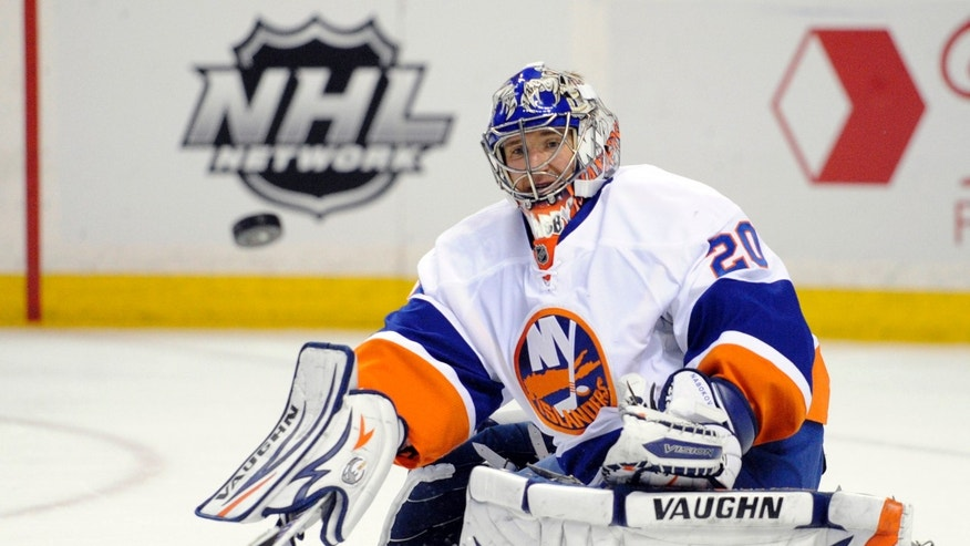 New York Islanders goaltender Evgeni Nabokov, of Russia, eyes the puck during the first period of an NHL hockey game against the Buffalo Sabres in Buffalo, N.Y., Friday, April 26, 2013. (AP Photo/Gary Wiepert)