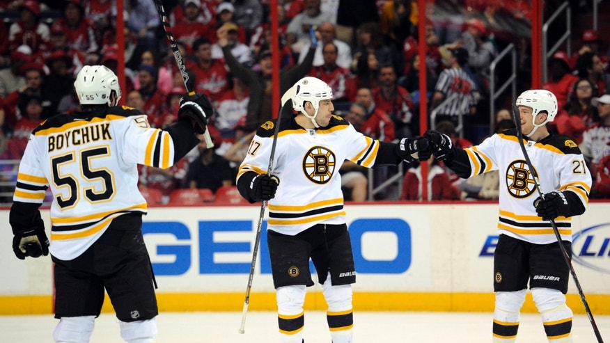 Boston Bruins left wing Milan Lucic (17) celebrates his goal with teammates Andrew Ference (21) and Johnny Boychuk (55) during the first period of an NHL hockey game against the Washington Capitals, Saturday, April 27, 2013, in Washington. (AP Photo/Nick Wass)