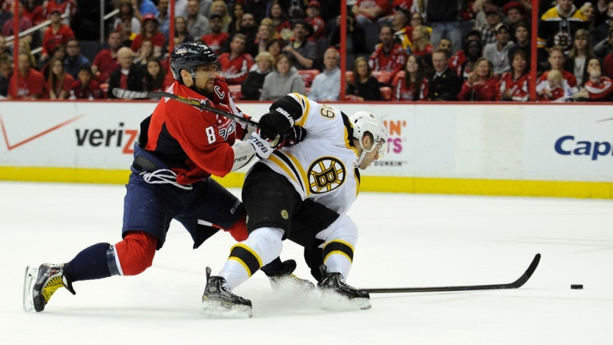 Washington Capitals left wing Alex Ovechkin (8), of Russia, battles for the puck against Boston Bruins center Rich Peverley, right, during the second period of an NHL hockey game, Saturday, April 27, 2013, in Washington. (AP Photo/Nick Wass)