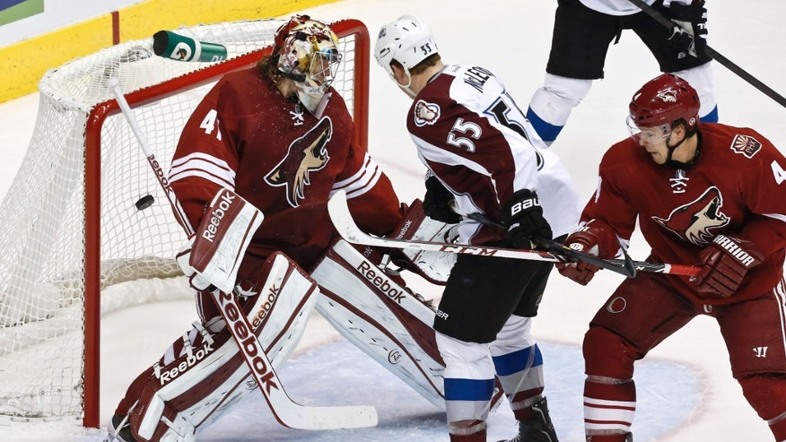 Phoenix Coyotes' Mike Smith, left, gives up a goal to Colorado Avalanche's P.A. Parenteau as the Avalanches' Cody McLeod (55) and Coyotes' Zbynek Michalek (4), of the Czech Republic, both look on during the first period in an NHL hockey game, on Friday, April 26, 2013, in Glendale, Ariz. (AP Photo/Ross D. Franklin)