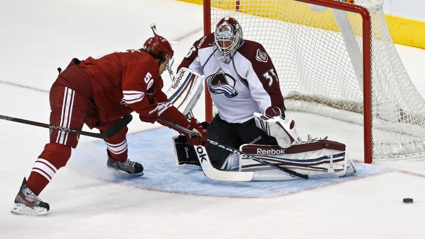 Colorado Avalanche's Jean-Sebastien Giguere (35) makes a save on a shot by Phoenix Coyotes' Antoine Vermette (50) during the first period in an NHL hockey game, on Friday, April 26, 2013, in Glendale, Ariz. (AP Photo/Ross D. Franklin)